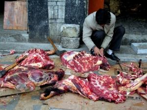 A butcher prepares yak meat outside the Potala Palace
