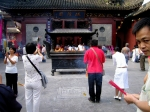 Chinese Tourists burn incense at the Old Town Temple - Shanghai, China