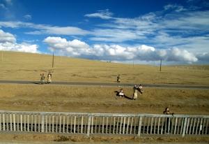 Tibetan Pilgrams wave at the Quinghai Tibet Railway Train