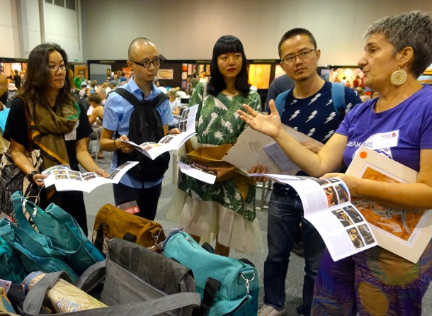 Chinese Curators learn about Indigenous Cultural Enterprize from Felicity Wright, Manager Injaluk Arts at the Darwin Aboriginal Art Fair